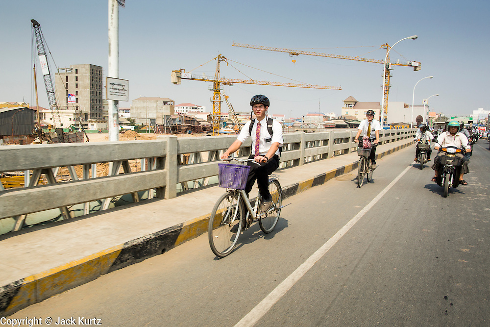 "30 JANUARY 2013 - PHNOM PENH, CAMBODIA: Missionaries from the Church of Latter Day Saints (Mormons) peddle their bikes across a bridge in Phnom Penh, Cambodia. It is customary for Mormon youth to go on a 2 year ""mission"" to evangelize and convert others to their religion. As many 75,000 missionaries served the church outside of the US in 2011.    PHOTO BY JACK KURTZ"