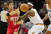 March 23, 2010; Cleveland, OH, USA; New Jersey Nets center Brook Lopez (11) makes a pass around Cleveland Cavaliers point guard Daniel Gibson (1) during overtime at Quicken Loans Arena. The Nets beat the Cavaliers 98-94 in overtime. Mandatory Credit: Jason Miller-US PRESSWIRE