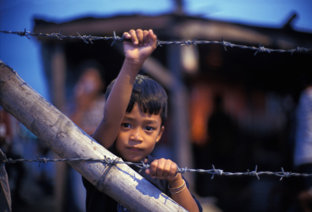 Philippines, Boy along the barbed wire fence of the cargo port in Bacolod, Negros Island.