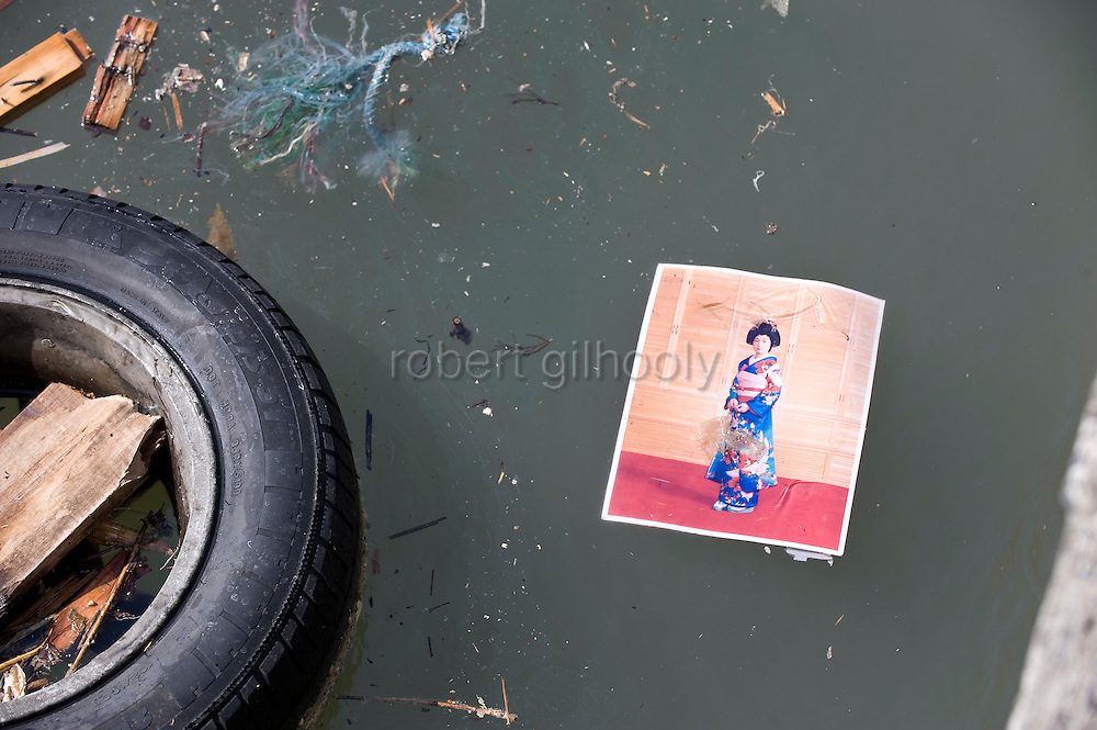 A photo of a kimono-clad woman floats next to a tire in the bay at Imeshi village on the Oshika Peninsula, Miyagi Prefecture, Japan on 19 March, 2011.  Photographer: Robert Gilhooly