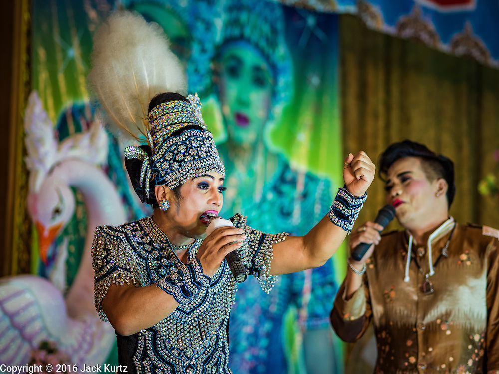 """30 JANUARY 2016 - NONTHABURI, NONTHABURI, THAILAND:  A """"likay"""" opera performance at Wat Bua Khwan in Nonthaburi, north of Bangkok. Likay is a form of popular folk theatre that includes exposition, singing and dancing in Thailand. It uses a combination of extravagant costumes and minimally equipped stages. Intentionally vague storylines means performances rely on actors' skills of improvisation. Like better the known Chinese Opera, which it resembles, Likay is performed mostly at temple fairs and privately sponsored events, especially in rural areas. Likay operas are televised and there is a market for bootleg likay videos and live performance of likay is becoming more rare.    PHOTO BY JACK KURTZ"""