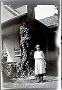 young adult woman standing in front of house 1920s USA