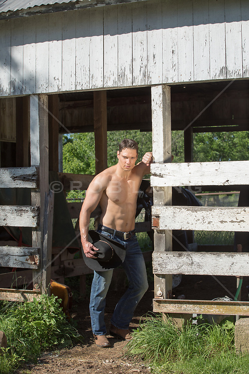 shirtless cowboy by a rustic barn