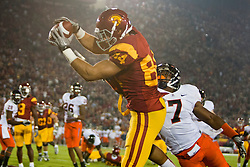 September 11, 2010; Los Angeles, CA, USA;  Southern California Trojans tight end Jordan Cameron (84) catches the ball for a touchdown past Virginia Cavaliers safety Corey Mosley (7) during the second quarter at the Los Angeles Memorial Coliseum.
