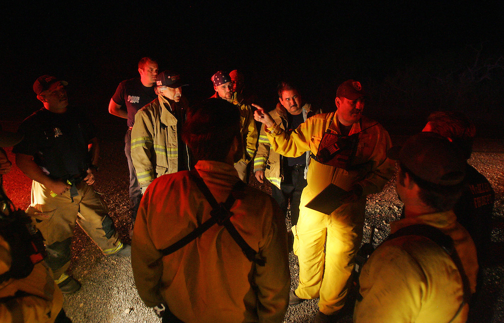 San Manuel, TX - 18 Mar 2008 -.US Fish & Wildlife and McAllen firefighters coordinate a plan to protect residences along Brushline Rd. after the fire jumped US 281 and continued spreading east..Photo by Alex Jones / ajones@themonitor.com