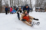 Curtis and Rubin Millsap get a push from Bret Gaertner and Isabella Millsap while sledding down their neighbor's hill on Thursday, January 5, 2017.