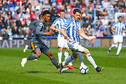 Eric Durm of Huddersfield Town (37) and Demarai Gray of Leicester City (7) in action during the Premier League match between Huddersfield Town and Leicester City at the John Smiths Stadium, Huddersfield, England on 6 April 2019.