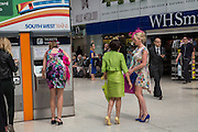 BUYING TICKETS FROM THE AUTOMATED TICKET MACHINES, Royal Ascot racegoers at Waterloo station. London. 20 June 2013.