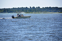 Recreational boaters motor past Swansboro along the White Oak River.