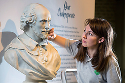 © Licensed to London News Pictures. 21/4/2016. Birmingham, UK. Rare and unseen Shakespeare items, including the first Folio are to go on display in a free exhibition at Birmingham Library from tomorrow. Pictured, Jennifer Bell cleans the statue that has sat in the Shakespeare Memorial Room at the library which will be one of the first items visitors will see. Photo credit : Dave Warren/LNP
