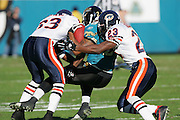 JACKSONVILLE, FL - DECEMBER 12:  Running back Fred Taylor #28 of the Jacksonville Jaguars (carried the ball 21 times for 79 yards rushing and caught 4 passes for 23 yards) gets gang tackled on this play by Jerry Azumah #23 and Charles Tillman #33 of the Chicago Bears on December 12, 2004 at Alltel Stadium in Jacksonville, Florida. The Jags defeated the Bears 22-3. ©Paul Anthony Spinelli *** Local Caption *** Fred Taylor; Jerry Azumah;Charles Tillman