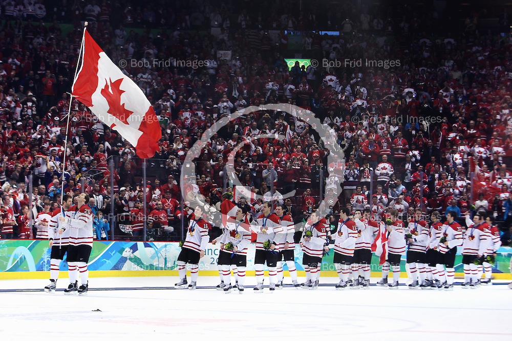 28 February 2010: Canada's Chris Pronger #20 celebrates the victory by carrying the Canadian flag around the ice at the end of the Gold medal Hockey Final between the United States and Canada during the Vancouver 2010 Winter Olympics  in Vancouver,  British Columbia, Canada.  Final score in Overtime: Canada 3 - USA 2 - Canada wins the Gold Medal and the USA Silver.
