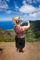 Middle aged woman taking a digital picture from a viewpoint overlooking Kalalau Valley on the na Pali Coast, Kauai, Hawaii, USA.