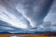 Wave clouds or common lenticular clouds loom over the Eastern Alaska Range and the Maclaren Glacier in the Maclaren River Valley in Interior Alaska in late fall. Evening.