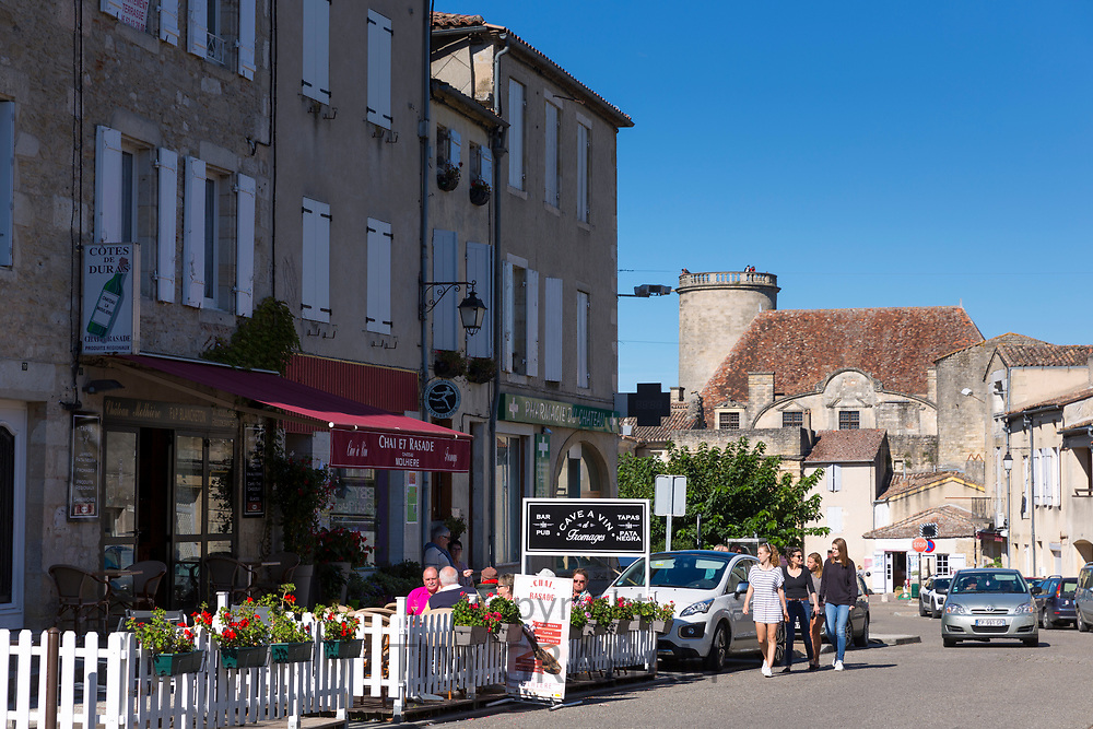 Tourists at cafe bar restaurant in ancient 13th Century bastide fortified town of Duras in Aquitaine, France