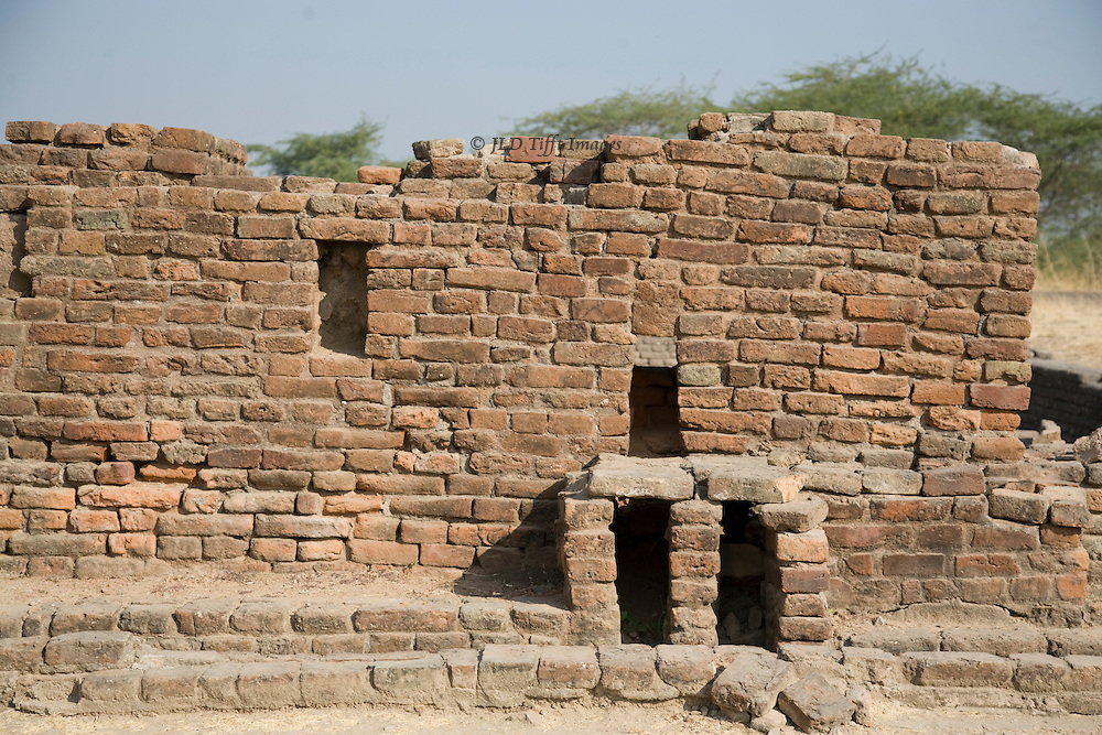 Harappan brick wall at Lothal, showing the side of a building with drains at the bottom of the wall.  Harappan bricks are larger than modern bricks, and of varying sizes.
