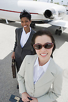 Portrait of two mid-adult businesswomen in front of private plane, elevated view.