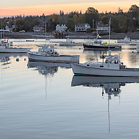 At first light, harborside houses overlook the lobster boats of the fishing fleet, in Bernard, Maine.