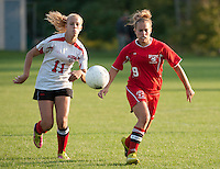 Alex Sorrell and Kim Allen charge for the ball during Tuesday evenings NHIAA soccer matchup at Robbie Mills Sports Complex.  (Karen Bobotas/for the Laconia Daily Sun)