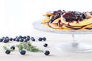 Fresh homemade blueberry pancakes on cake stand, covered with blueberry jam.
