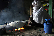 Khandra, a 55-year-old Bedouin woman, is making the bread in her house in the unrecognised village of Wadi el Na'am, pop. 4000, close to Beer Sheva, the capital of the Negev, a large deserted area in the south of Israel.  Wadi el Na'am is located near a large industrial site, Ramat Hovav, and has no infrastructure or electric energy. Water is provided only via storage tanks. It has no health services as the only clinic is deemed illegal and bound to be demolished, as the rest of the structures in the area. Numbering around 200.000 in Israel, the Bedouins constitute the native ethnic group of these areas, they farm, grow wheat, olives and live in complete self sufficiency. Many of them were in these lands long before the Israeli State was created and their traditional lifestyle is now threatened by subtle Governmental policies. The seven Bedouin towns already built are all between the 10 more impoverished towns in Israel.