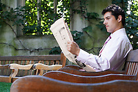 Businessman sitting on bench in park garden reading paper