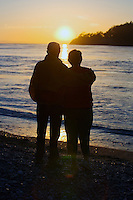 Silhouette of couple watching sunset on beach.