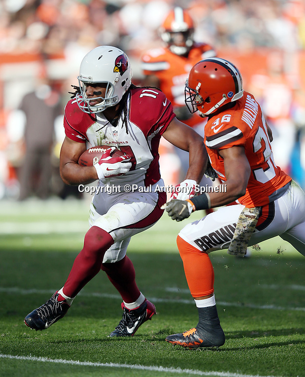 Arizona Cardinals wide receiver Larry Fitzgerald (11) runs with the ball after catching a late second quarter pass while Cleveland Browns free safety K'Waun Williams (36) closes in and strips Fitzgerald of the ball causing a fumble and a turnover that stops a potential scoring drive during the 2015 week 8 regular season NFL football game against the Cleveland Browns on Sunday, Nov. 1, 2015 in Cleveland. The Cardinals won the game 34-20. (©Paul Anthony Spinelli)