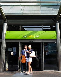 © Licensed to London News Pictures. 14/09/2016. Portsmouth, UK.  A couple exit the Job Centre Plus in Portsmouth this morning following the latest unemployment figures showing that the rate remains unchanged at 4.9% following Brexit. The number of people unemployed fell by 190,000 from the previous year, while the number of people in employment rose 174,000, taking the total to 31.77 million. Photo credit: Rob Arnold/LNP