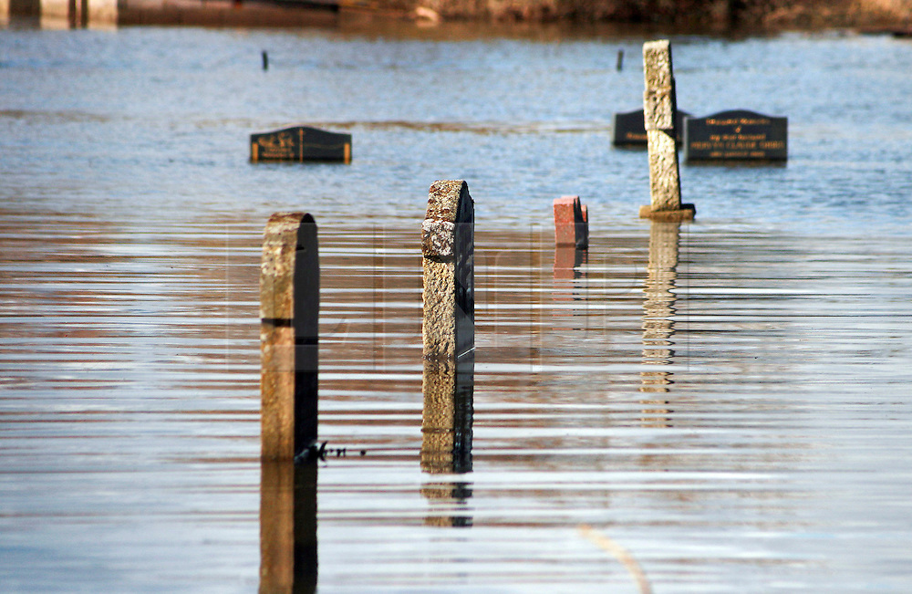 © London News Pictures. 24/02/2014. Moorland, UK. Flood water covering graves in a church graveyard in Moorland on the Somerset Levels, which continues to suffer from sever flooding. Photo credit: Jason Bryant/LNP