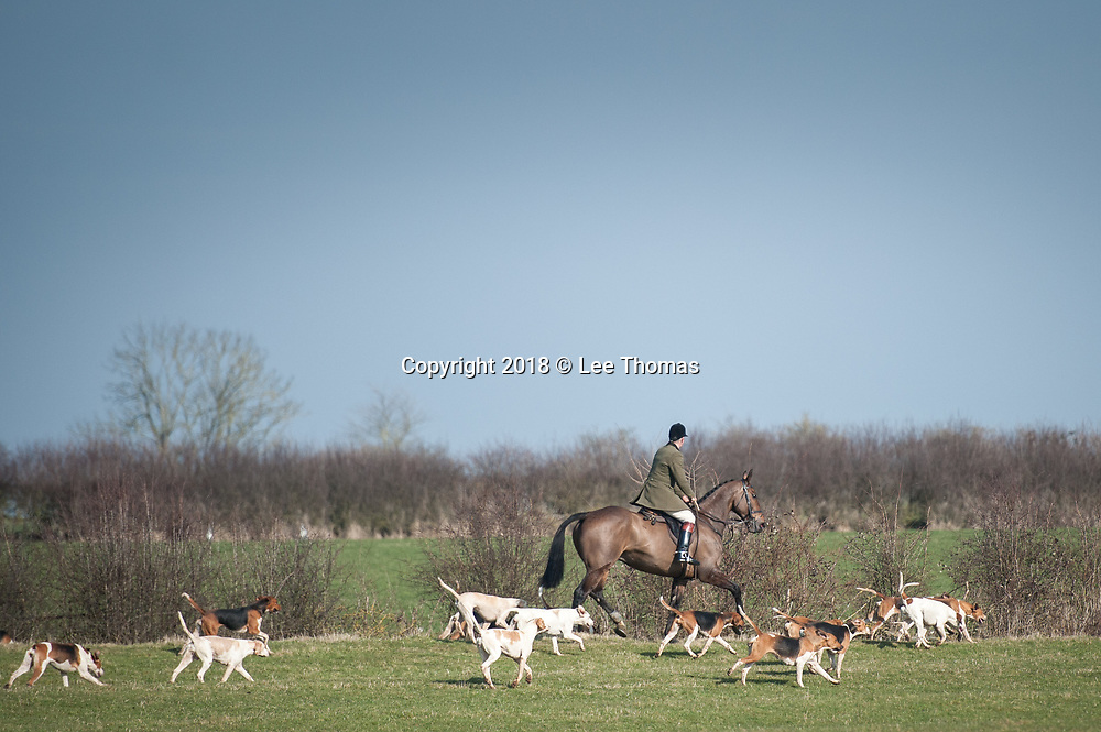 Oxhill, Warwickshire, UK. 24th February 2018. Members of the Warwickshire Hunt congregate at Oxhill, Warwickshire, on a bright but cold winter's day. The meet comes a day before several demonstrations are to be held by National Dis-Trust, a  campaign group against hunting on National Trust land. At present, the National Trust allows so-called 'trail hunts' on its land, where hounds are supposedly following a scent but National Dis-Trust supporters claim many wild animals, including foxes, hares and deer, end up being chased and killed at these events. Pictured: The Warwickshire Hunt ride over land near to Oxhill.  // Lee Thomas, Tel. 07784142973. Email: leepthomas@gmail.com  www.leept.co.uk (0000635435)