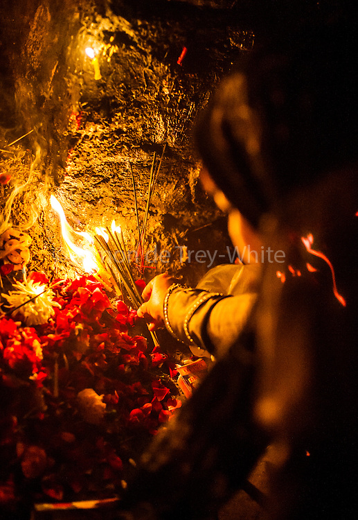 15th January 2015, New Delhi, India. A woman lights an incense stick as part of her devotion as she asks for wishes to be granted by Djinns in the ruins of Feroz Shah Kotla in New Delhi, India on the 15th January 2015<br /> <br /> PHOTOGRAPH BY AND COPYRIGHT OF SIMON DE TREY-WHITE a photographer in delhi. + 91 98103 99809. Email:simon@simondetreywhite.com<br /> <br /> People have been coming to Firoz Shah Kotla to leave written notes and offerings for Djinns in the hopes of getting wishes granted since the late 1970's. Jinn, jann or djinn are supernatural creatures in Islamic mythology as well as pre-Islamic Arabian mythology. They are mentioned frequently in the Quran  and other Islamic texts and inhabit an unseen world called Djinnestan. In Islamic theology jinn are said to be creatures with free will, made from smokeless fire by Allah as humans were made of clay, among other things. According to the Quran, jinn have free will, and Iblīs abused this freedom in front of Allah by refusing to bow to Adam when Allah ordered angels and jinn to do so. For disobeying Allah, Iblīs was expelled from Paradise and called &quot;Shayṭān&quot; (Satan).They are usually invisible to humans, but humans do appear clearly to jinn, as they can possess them. Like humans, jinn will also be judged on the Day of Judgment and will be sent to Paradise or Hell according to their deeds. Feroz Shah Tughlaq (r. 1351&ndash;88), the Sultan of Delhi, established the fortified city of Ferozabad in 1354, as the new capital of the Delhi Sultanate, and included in it the site of the present Feroz Shah Kotla. Kotla literally means fortress or citadel.