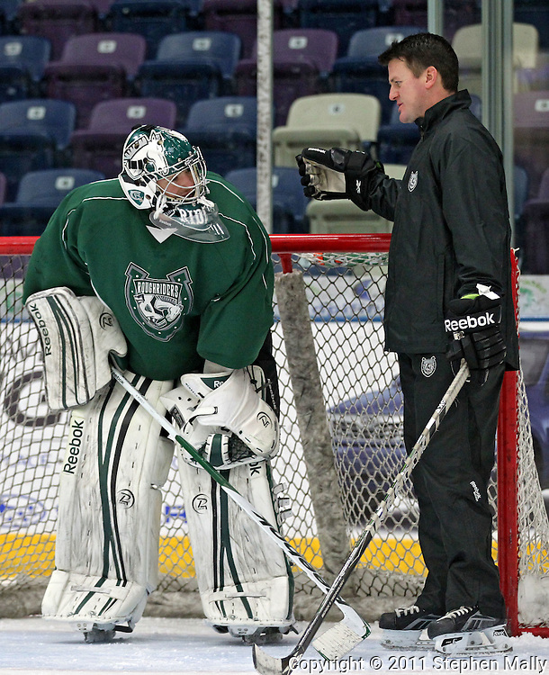 Goaltending coach Scott Meyer (right) talks with RoughRiders goalie Matt McNeely after a rapid-fire drill during a practice at the Cedar Rapids Ice Arena, 1100 Rockford Road SW, in Cedar Rapids on Tuesday, December 13, 2011. (Stephen Mally/Freelance)