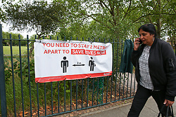 © Licensed to London News Pictures. 30/06/2020. London, UK. A woman walks past 'YOU NEED TO STAY 2 METERS APART TO SAVE LIVES NOW' banner displayed outside Chestnuts Park in Harringay. Haringey in north London is amongst 36 areas in England where COVID-19 cases are rising according to Public Health England. Photo credit: Dinendra Haria/LNP