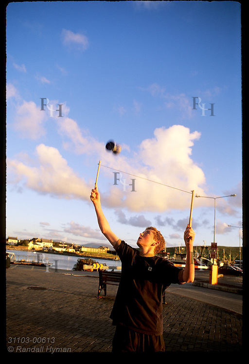 Teenage boy flings wooden 'diablo' spindle into air at sunset in town of Dingle, Ireland