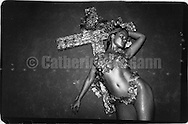 January 22, 1990:  A woman woman with silver body paint poses for a photo in front of a cross on the opening night of nightclub Morrissey in New York City