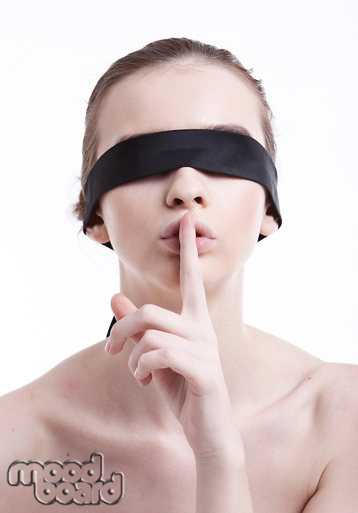 Shirtless young woman with blindfold gesturing to be silent against white background