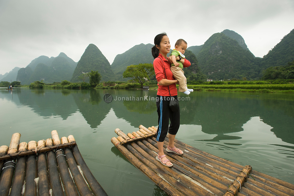 A tourist woman holds her baby while standing on a bamboo raft in the middle of the Li River near Yangshuo, China (Model Released, Rachel Ouyang, Tintin Ouyang).