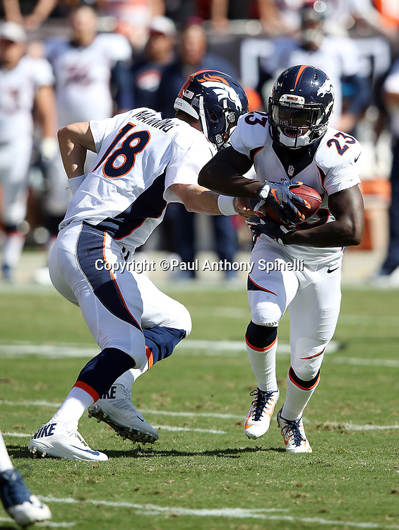 Denver Broncos running back Ronnie Hillman (23) takes a handoff from Denver Broncos quarterback Peyton Manning (18) during the 2015 NFL week 5 regular season football game against the Oakland Raiders on Sunday, Oct. 11, 2015 in Oakland, Calif. The Broncos won the game 16-10. (©Paul Anthony Spinelli)