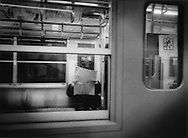 Absorbed in a newspaper, commuter train near Tokyo, Japan.