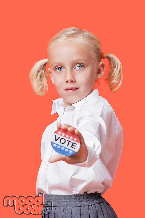 "Portrait of a young girl holding ""Vote"" sign over orange background"
