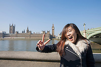 Portrait of young woman gesturing V-sign against Big Ben at London; England; UK