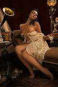 Scene set in Paris circa Paris 1910. A beautiful young woman listens to music while enjoying a glass of absinthe and is carried away with pleasure. Model - Sabrina Sin
