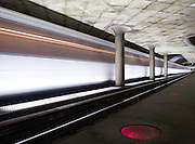 Image of a Washington, D.C. metro train speeding past a metro station.