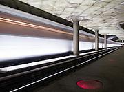 Image of a Washington, D.C. metro train speeding past a metro station.