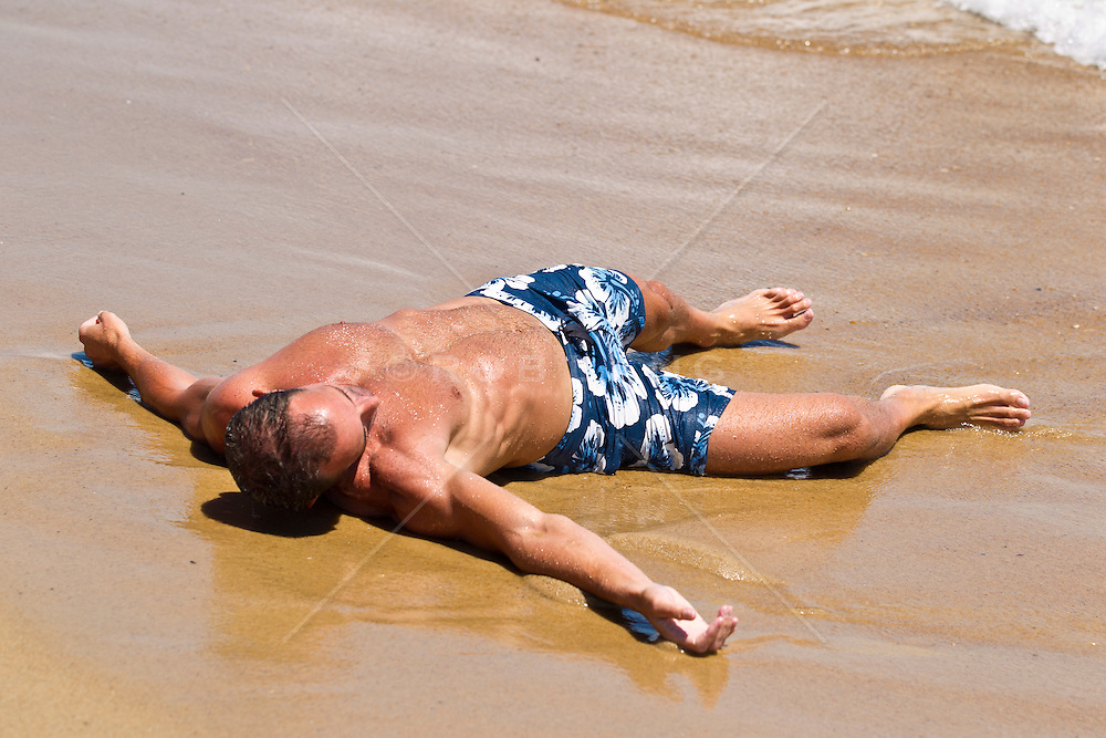 man cooling off in the sand and water in East Hampton, NY