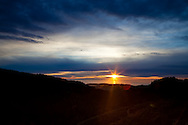 The sun sets over the Pacific Ocean beyond green hills, Purisima Creek Redwoods Open Space Preserve