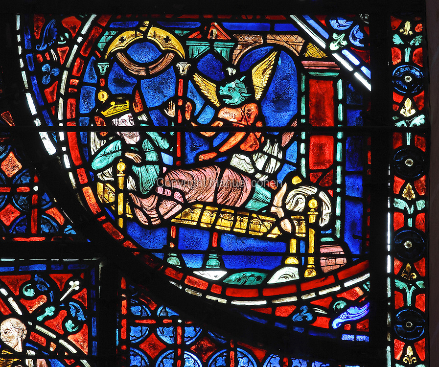 The boat containing the relics of St Stephen passes an island at the moment of an earthquake. The demon, with red body, green face and yellow wings, tries to persuade the King to burn the ship for having caused the earthquake. Section of the demon speaking to the King, 1220-25, from the Life of St Stephen and transferral of his relics window in the ambulatory of Chartres Cathedral, Eure-et-Loir, France. This window, unusually dominantly red in colour, tells the story of the life of St Stephen, the first Christian martyr, who died c. 36 AD and whose relics are held at Chartres. It is situated in the chapel dedicated to martyrs. Chartres cathedral was built 1194-1250 and is a fine example of Gothic architecture. Most of its windows date from 1205-40 although a few earlier 12th century examples are also intact. It was declared a UNESCO World Heritage Site in 1979. Picture by Manuel Cohen