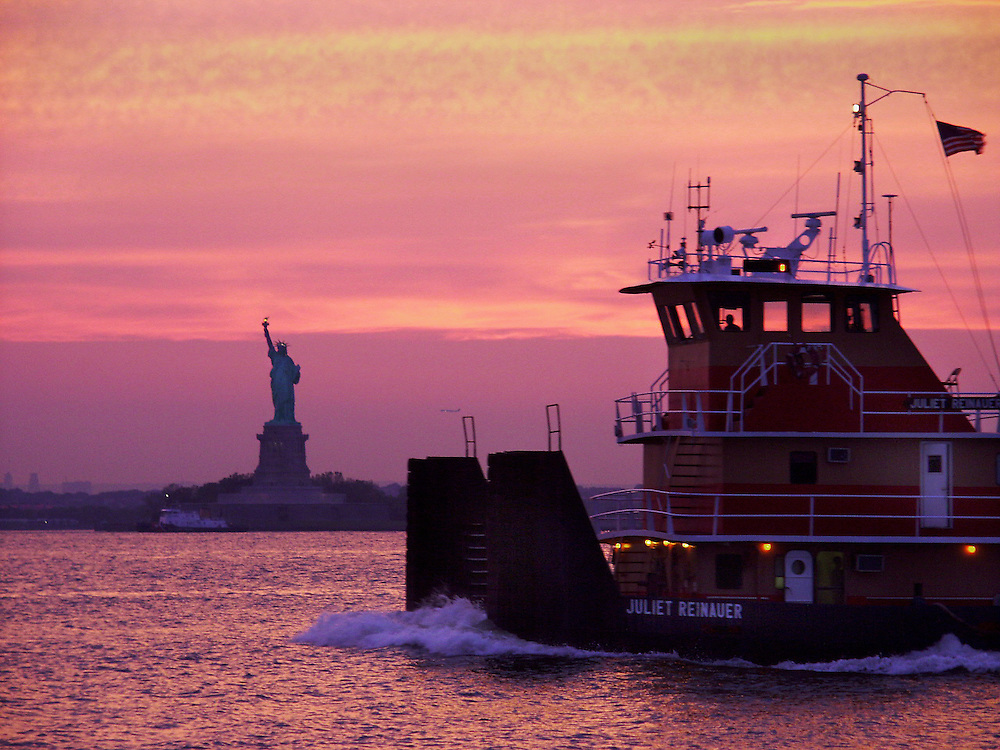 Tug boat passing by Lady Liberty just after a glorious sunset.