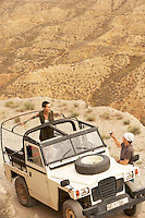 Man photographing woman standing in four wheel drive car on edge of cliff elevated view